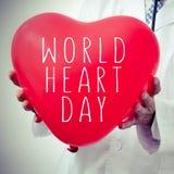 Doctor con un globo en forma de corazón con el día del corazón del mundo del texto Imagen de archivo