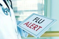 Doctor con una tableta con la alarma de la gripe del texto Imagen de archivo libre de regalías
