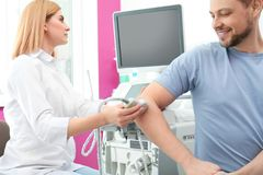 Doctor conducting ultrasound examination of elbow joint in clinic royalty free stock image