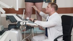 The doctor conducts ultrasound examination of the patient`s legs. Methods of diagnosing varicose veins. The specialist. Checks the patient`s veins. Phlebeurysm stock footage