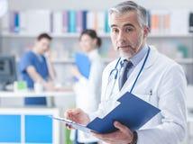 Doctor confiado que comprueba informes médicos fotos de archivo