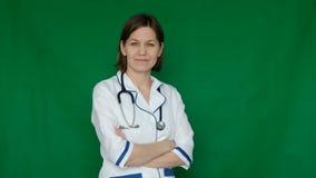 Doctor confiado sonriente de la mujer en la capa del laboratorio que mira la cámara en una pantalla verde, llave de la croma metrajes