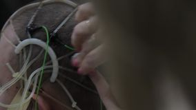 The doctor connects the electronic sensors to the patient`s head. Progressive medical technologies. Nanotechnology