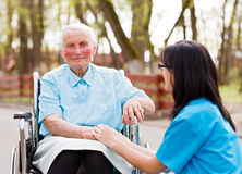 Doctor Consoling Elderly Lady Stock Photo