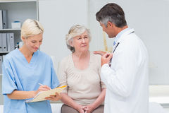 Doctor consoling patient while nurse writing reports. Male doctor consoling patient while nurse writing reports in clinic Stock Photos
