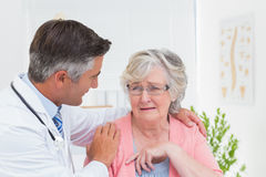 Doctor consoling senior patient in clinic Stock Photography