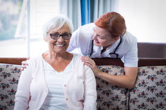 Doctor consoling senior woman Stock Images