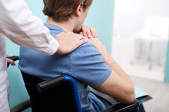 Doctor consoling young man sitting in wheelchair. Female doctor consoling young man sitting in wheelchair stock photos