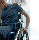 Doctor consoling young man sitting in wheelchair. Female doctor consoling sad man sitting in wheelchair stock photography