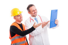 Doctor and constructor showing something on clipboard and smilin Stock Images
