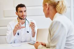 Doctor in consultation. With patient giving advice stock photos