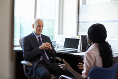 Doctor In Consultation With Female Patient In Office Stock Photos