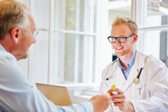 Doctor in consultation with patient. Doctor receiving urine sample in consultation with patient royalty free stock images