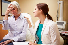 Doctor In Consultation With Senior Concerned Female Patient. Putting Hand On Shoulder royalty free stock photography