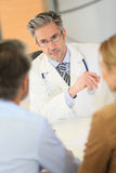 Doctor consulting couple in hospital office Stock Images