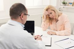 Doctor consulting woman in hospital stock images