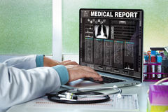Doctor consulting a medical history on a computer Stock Images
