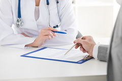 Doctor consulting patient. Female doctor holding consulting patient showing documents Stock Photo