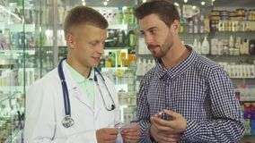 Doctor consulting patient about pills. Doctor reading pills instruction to man. Patient holding pills and asking questions. People are standing in drugstore royalty free stock photos