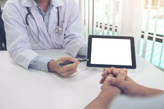Doctor consulting patient and recommend treatment methods and how to rehabilitate the body, presenting results on tablet computer Royalty Free Stock Images