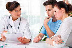 Doctor consults a young couple. Doctor women offering medical advices to a young couple in office