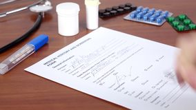 Doctor continue writing a medical history and screening form of the patient stock footage