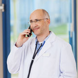 Doctor Conversing On Cordless Phone In Clinic Royalty Free Stock Photo