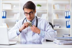 The doctor in corruption concept with being offered bribe. Doctor in corruption concept with being offered bribe Royalty Free Stock Photography