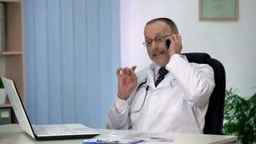 Doctor corrupto de la astucia que hace alusión al soborno en la conversación telefónica con el paciente imágenes de archivo libres de regalías