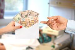 Doctor corrupto que toma el soborno de un paciente delante de una cama de hospital imagen de archivo