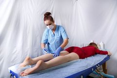 Doctor Cosmetician Doing Shugaring On The Back Of The Left Leg A Young Woman In A Red Dress Stock Image