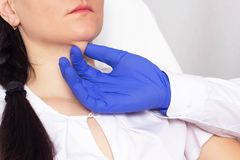 Doctor cosmetologist checks the skin for elasticity on a double chin in a girl, close-up, cosmetology, resilience royalty free stock image