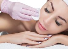 The doctor cosmetologist cleanses with a tonic the face skin of a beautiful, young woman in a beauty salon. Cosmetology skin care Royalty Free Stock Image