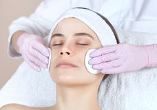 The doctor cosmetologist cleanses with a tonic the face skin of a beautiful, young woman in a beauty salon. Cosmetology skin care Stock Image