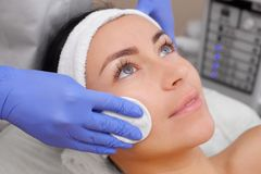 The doctor cosmetologist cleanses with a tonic the face skin. Of a beautiful, young woman in a beauty salon.Cosmetology skin care Royalty Free Stock Photography