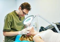 Doctor cosmetologist examining woman skin Stock Photos
