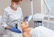 The doctor-cosmetologist makes the apparatus a procedure of Hardware face cleaning with a soft rotating brush of a beautiful, youn. G women in a beauty salon Stock Image