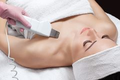 The doctor-cosmetologist makes the apparatus a procedure of ultrasound cleaning of the decollete skin of a beautiful, young woman. In a beauty salon Stock Photos