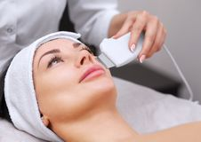 The doctor-cosmetologist makes the apparatus a procedure of ultrasound cleaning. Of the facial skin of a beautiful, young woman in a beauty salon. Cosmetology Royalty Free Stock Photography