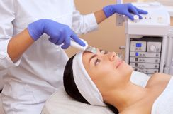 The doctor-cosmetologist makes the apparatus a procedure of ultrasound cleaning of the facial skin of a beautiful, young woman in Stock Photos