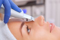 The doctor-cosmetologist makes the apparatus a procedure of ultrasound cleaning of the facial skin. Of a beautiful, young woman in a beauty salon. Cosmetology Stock Photo