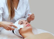 The doctor-cosmetologist makes the apparatus a procedure of ultrasound cleaning of the facial skin of a beautiful, young woman. The doctor-cosmetologist makes Stock Photos