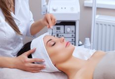 The doctor-cosmetologist makes the face vacuum therapy on the cheek of a beautiful, young woman in a beauty salon Stock Photography