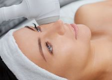 The doctor-cosmetologist makes the procedure Cryotherapy of the facial skin of a beautiful, young woman in a beauty salon. Cosmetology and professional skin Stock Photos