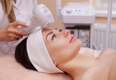 The doctor-cosmetologist makes the procedure Cryotherapy of the facial skin of a beautiful, young woman in a beauty salon. Stock Photos