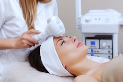 The doctor-cosmetologist makes the procedure Cryotherapy of the facial skin of a beautiful, young woman in a beauty salon. Cosmetology and professional skin Stock Photography