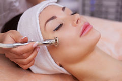 The doctor-cosmetologist makes the procedure Microdermabrasion of the facial skin of a beautiful, young woman in a beauty salon. Stock Photography