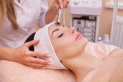The doctor-cosmetologist makes the procedure Microdermabrasion of the facial skin of a beautiful, young woman Royalty Free Stock Images