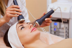 The doctor-cosmetologist makes the procedure an ultrasonic cleaning of the facial skin of a beautiful, young woman Stock Photo