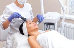 The doctor-cosmetologist makes the procedure an ultrasonic cleaning of the facial skin of a beautiful, young woman royalty free stock image